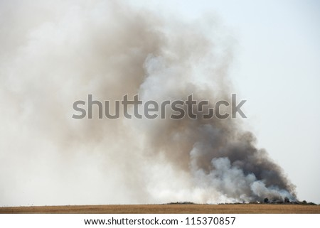 Toxic black smoke from fire in dung-hill emitting poison in the air - stock photo