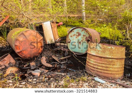 Toxic waste barrels left behind in a forest - stock photo