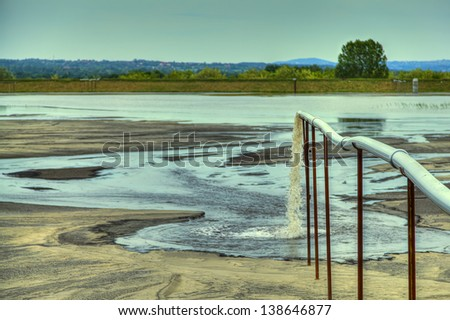 Toxic water stems from the pipe polluting the lake - stock photo