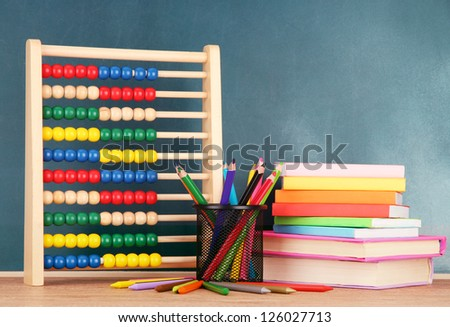 Toy abacus, books and pencils on table, on school desk background - stock photo