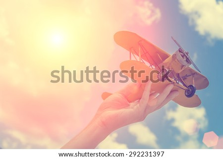 Toy airplane in hand - a symbol of travel and dreams - stock photo