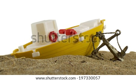 Toy boat with anchor on sand, isolated on white - stock photo