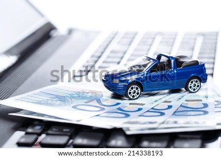 Toy car and banknotes over laptop keyboard - stock photo