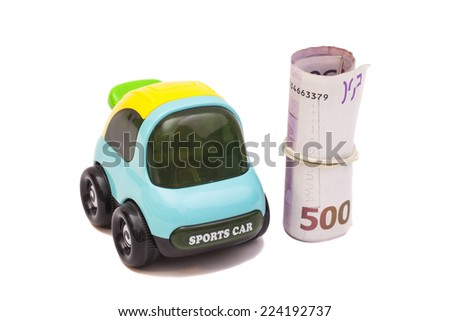 Toy car and roll of five hundred euro banknotes with a rubber band - stock photo