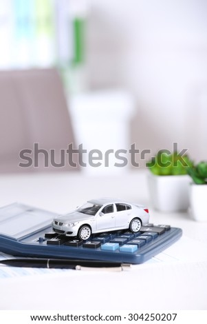 Toy car, documents and calculator on table. Car insurance concept - stock photo