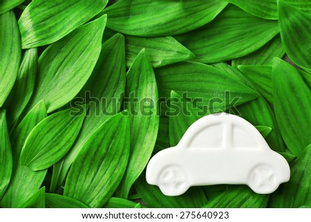 Toy car on green leaves background - stock photo