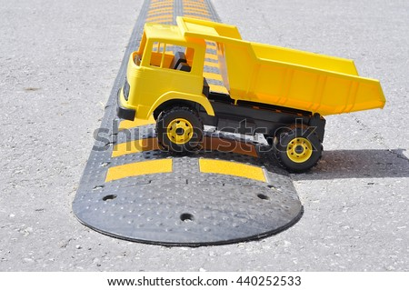 Toy car on the road on sleeping policeman - stock photo