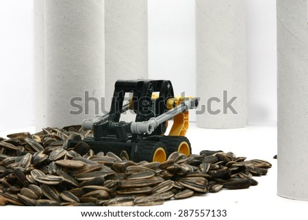 toy digger moves sunflower seeds - stock photo