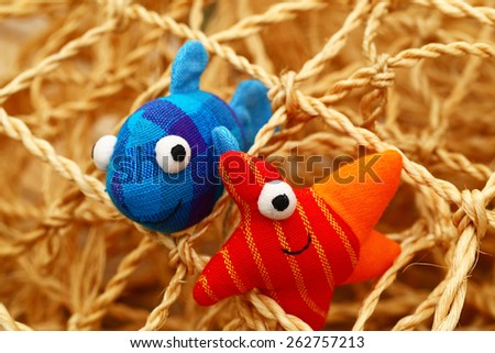 Toy fabric red starfish and blue fish on the background of decorative fishing net, close up - stock photo