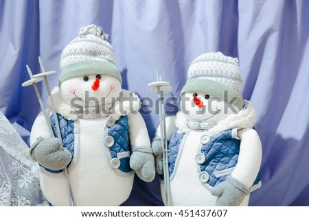 Toy figures of snowmen dressed like skiers - stock photo