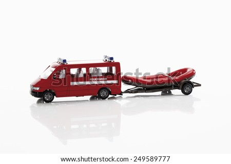 Toy fire truck with rubber raft on white background - stock photo