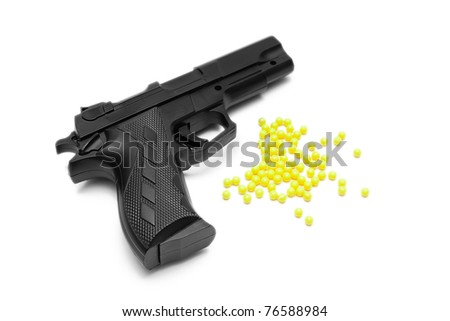 Toy gun with pellets isolated on white - stock photo
