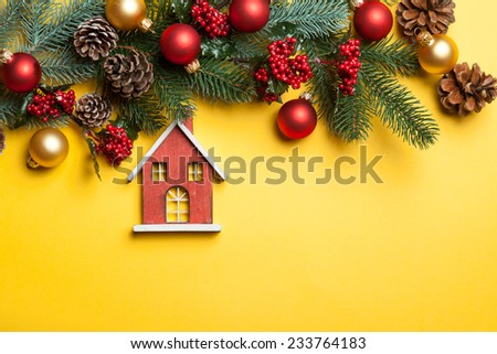 Toy house and pine branches with toys on yellow background. - stock photo