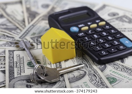 toy house, keys and calculator on the background dollars banknotes - stock photo