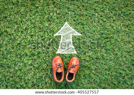 toy leather shoe on grass field texture background with drawing of arrow direction with copy space - stock photo