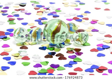 Toy marbles on white background, surrounded by so many multicolor hearts. - stock photo