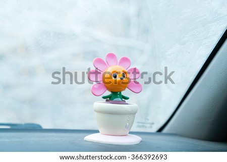 Toy on the dashboard in the car on the background of the frozen windshield glass - stock photo