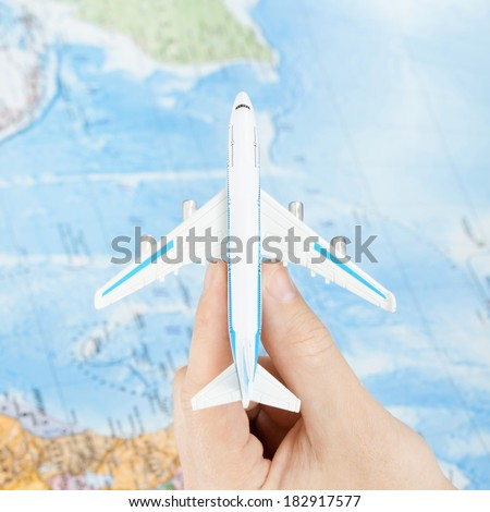 Toy plane in hand with world map on background - view from top - 1 to 1 ratio - stock photo