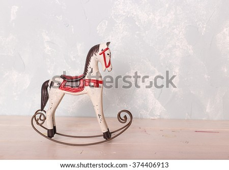 toy rocking white horse on the wooden floor against the backdrop of a blue wall - stock photo