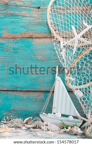 Toy sailboat with shells and fishing net on a rustic shabby wooden turquoise background - stock photo
