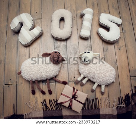 Toy sheep and 2015 handmade wooden background - stock photo