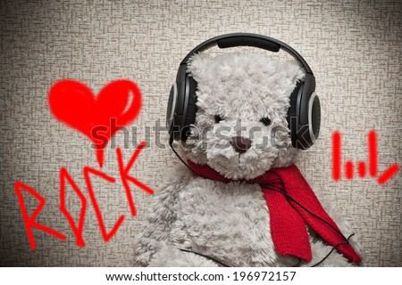 Toy teddy bear with a red scarf listening to music on headphones. Fan of Rock music - stock photo
