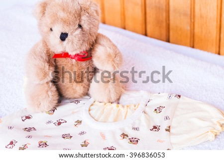 Toy teddy bear with baby clothing. Clean little child cloth on the wooden table in laundry. Blue cotton infant dry brown small toy. Birth newborn kid.   - stock photo