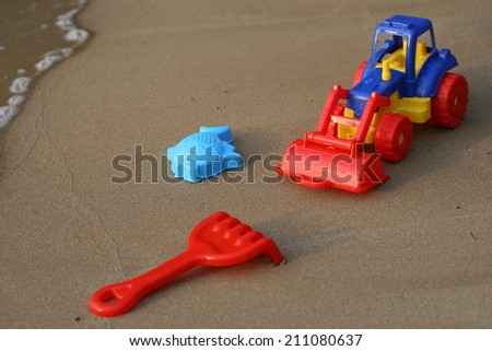 toy tractor on the sand beach summer vacation wheel rake bucket plastic fish - stock photo