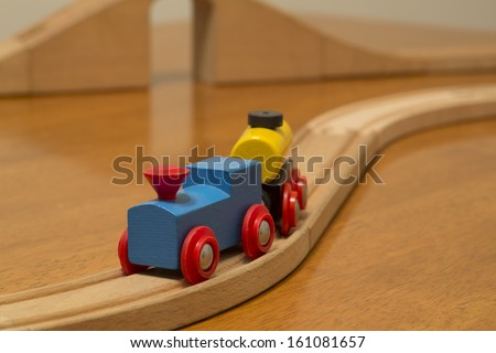 toy train on track and bridge in background - stock photo