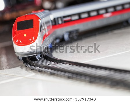 Toy train over railway, dynamic diagonal image, horizontal - stock photo