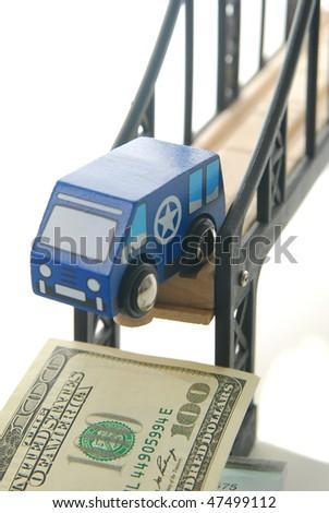 toy van driving off bridge focus on bill. - stock photo
