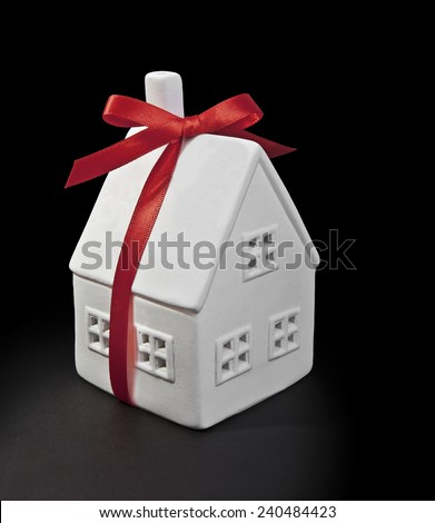 Toy white house with a red bow on a black background. Dream home. - stock photo