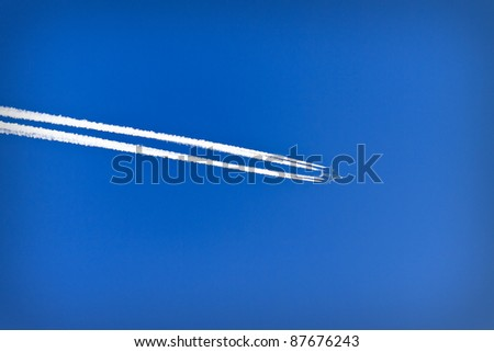 Trace of an airplane against blue sky - stock photo