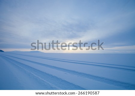 Traces of cars in the vast snowy wilderness. Lake Baikal in winter. - stock photo