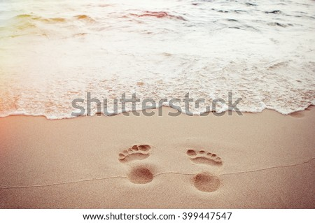 traces of feet on the sand - stock photo