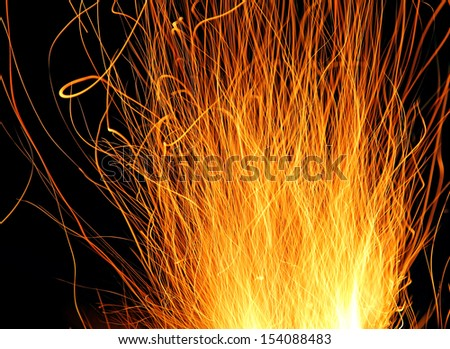 Traces of fire sparks above a campfire. - stock photo