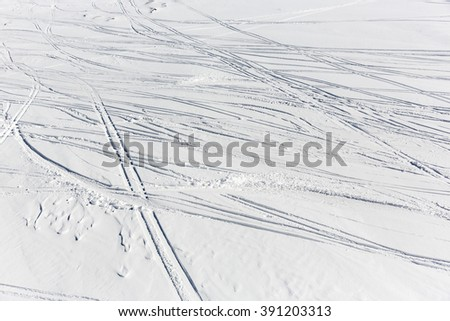 Traces of skiers are seen from above on a ski slope in a snowy mounatin peak. - stock photo