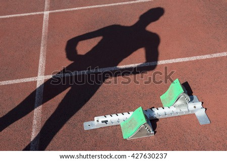 Track athlete casts shadow on starting blocks at the starting line of a race on a red running track - stock photo