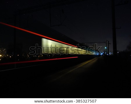 Track by a passing train. The photo was taken at night using long exposure. The picture shows a trace of a passing train. Picture is dynamic, so the train is in motion captured.  - stock photo