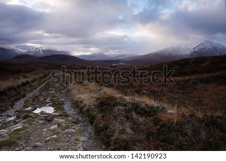 Track leading to distant hills on Rannoch Moor, nr Glencoe, Scottish Highlands, UK. Taken while walking along this rugged path after a wet start one morning in Autumn. - stock photo