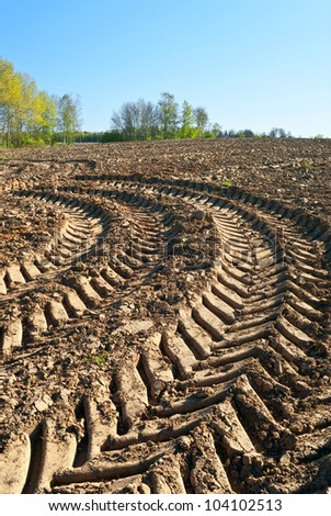 Track of a heavy tractor on plowed field - stock photo