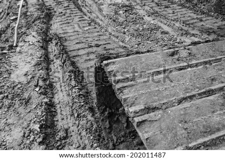 Track of a tractor on plowed field(Black and white) - stock photo