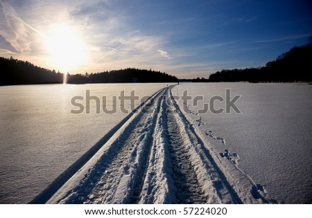 Track of snow mobile on the ice of a lake in winter - stock photo