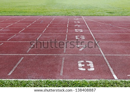 Track position number at the finishing line of a rubberized athletic running track.  - stock photo