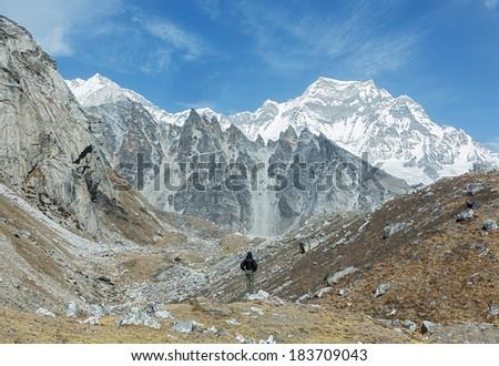 Tracker on the way in the ridge Mahalangur Himal near Cho Oyu with peak Guachung Kang (7952 m) in the background - Gokyo region, Nepal, Himalayas - stock photo