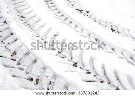 Tracks of car tires in defrosted snow  - stock photo