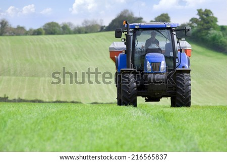 Tractor and fertilizer spreader in field - stock photo
