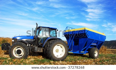 Tractor and trailer in a maize field during harvest time - stock photo