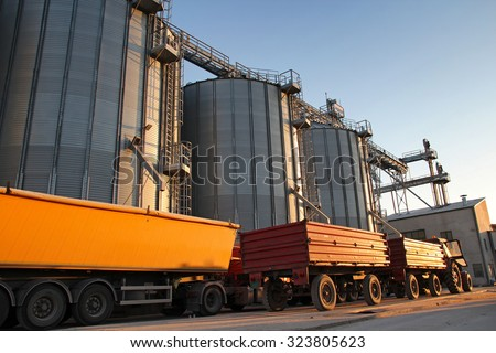 Tractor and Truck Beside Grain Silos. Commercial Steel Silos and Bins for Grain Storage. Loading maize, wheat or soybean into the metal silos for storage after the harvest. - stock photo