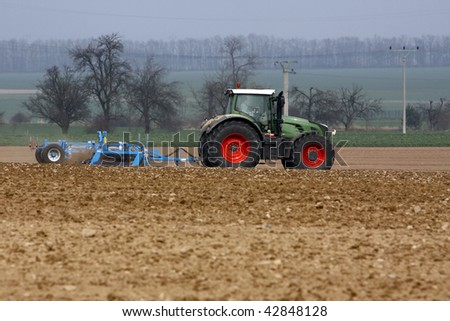 tractor at work on a field - stock photo